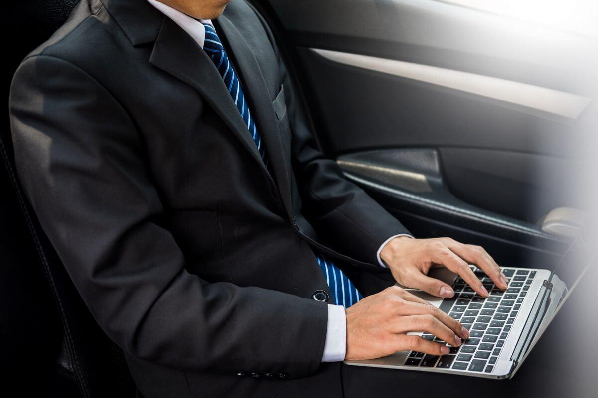 Mann mit Anzug und Laptop im Auto arbeitend